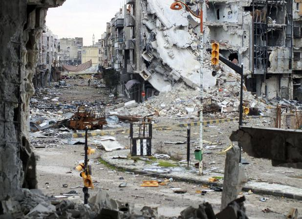 General view shows damaged buildings and street lights on a street in Homs