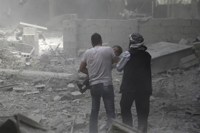 Men help an injured boy who survived what activists said were airstrikes by forces loyal to Syria's President Bashar al-Assad, in the Douma neighborhood of Damascus