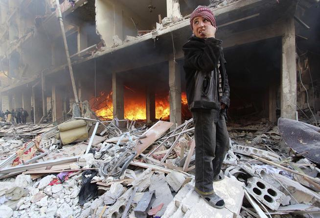 A boy stands on rubble as people try to put out a fire after what activists said were airstrikes and shelling by forces loyal to Syria's President Assad in Douma