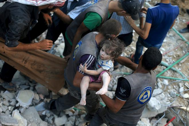 A medic carries an injured girl that survived from under debris caused by what activists said was barrel bombs dropped by forces loyal to Syria's President Bashar Al-Assad in Douma, Eastern Al-Ghouta, near Damascus, Syria