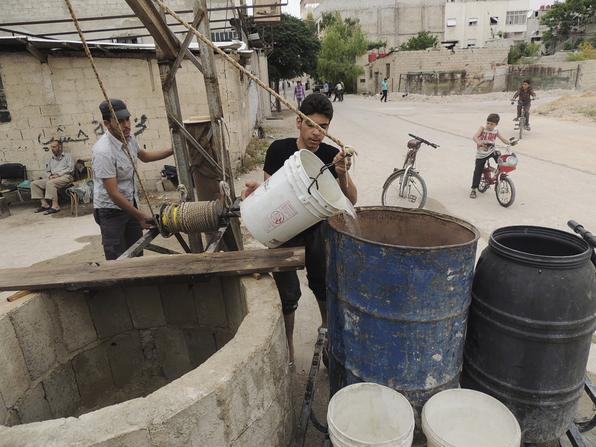 File picture of residents extracting water from a well in Arbeen